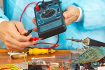 Serviceman checks board of electronic device with a multimeter in service workshop